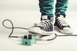 Rock player in sneakers stomp guitar overdrive pedal
